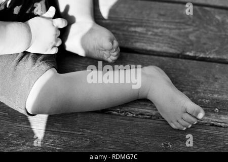 Low-section of baby boy sitting barefoot - Stock Image