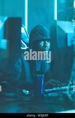 Serious young Afro-American hacker in hoodie sitting at table and typing on computer keyboard while composing data virus code - Stock Image