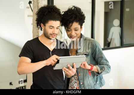 Couple using digital tablet together - Stock Image