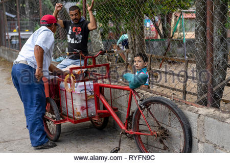 Elementary school student buys an ice cream cone from a bicycle cart vendor just outside the school fence. - Stock Image