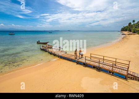A couple arrive on a golden sand beach of a paradise island along a jetty. - Stock Image