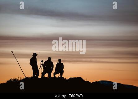 Group of three photographers taking photo against sunset sky - Stock Image