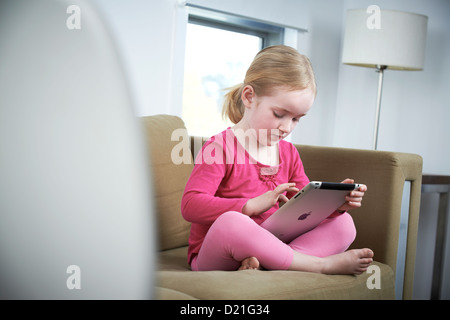 Little girl using ipad at home - Stock Image