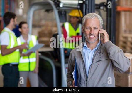 Warehouse manager talking on mobile phone and holding a clipboard - Stock Image