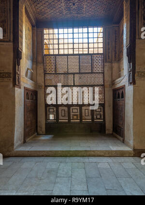 Interleaved wooden window (Mashrabiya), wooden embedded cupboards, and wooden decorated ceiling at ottoman historic Beit El Set Waseela building - Stock Image