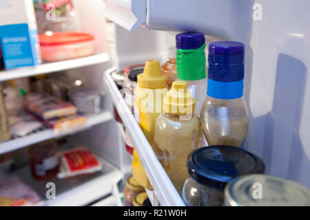Bottles and containers inside a fridge - Stock Image