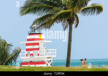 Miami Beach Florida South Pointe Park Atlantic Ocean urban public space seashore palm tree breeze blown frond man woman couple l - Stock Image