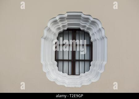 Isolated Round Window with Iron Bars Detail on a Cream Colored Wall Background in old City Antigua Guatemala - Stock Image