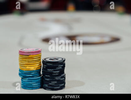 Two stacks of poker chips with defocused poker table in background. - Stock Image