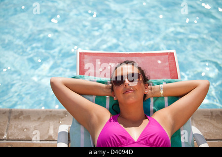 An attractive young woman in a bathing suit relaxing in the sun beside a swimming pool. - Stock Image