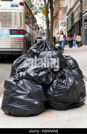 Piles of trash in black rubbish bags piled up on the pavement awaiting collection in a street in New York - Stock Image