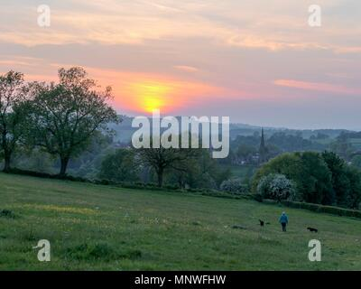 Derbyshire, UK. 19th May 2018. UK Weather: Woman's walking her dogs into a wonderful sunset over Ashbourne, Derbyshire, the gateway to the Peak District National Park Credit: Doug Blane/Alamy Live News - Stock Image