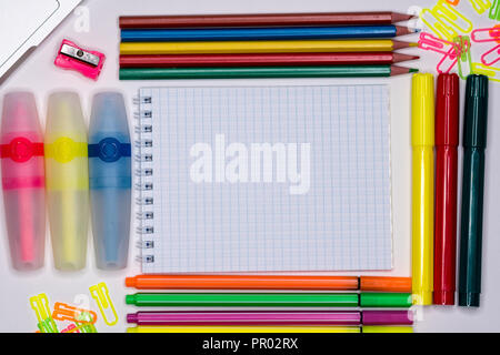 Notepad with text space, markers, pencils, paper clips on desctop - Stock Image