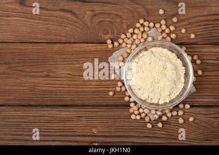Chickpea flour in a wooden spoon, chickpeas on old wooden background - Stock Image