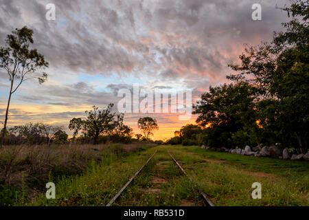 Fiery sky at sunset along a railway line, Mount Surprise, Queensland, QLD, Australia - Stock Image