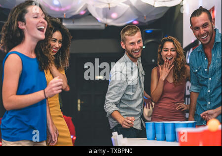Happy friends playing beer pong in a cocktail bar - Young millennials people having fun doing party alcohol games at night pub - Stock Image