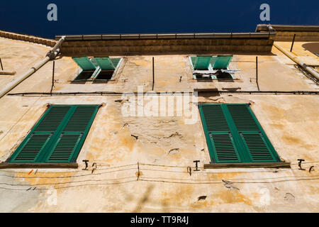 Old building facade with windows covered with green wooden louvered shutters, Villefranche-sur-Mer, Provence, France, Europe - Stock Image