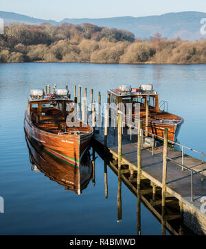 Tourist boats moored up a long the jetty on Derwentwater Lake in the Cumbrian lake district England UK - Stock Image
