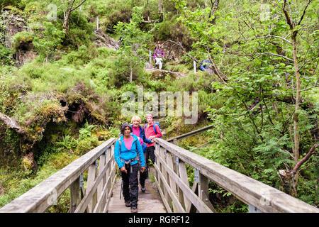 Senior hikers crossing footbridge across River Coe from Lost Valley or Coire Gabhail. Glen Coe Pass, Glencoe, Lochaber, Highland, Scotland, UK - Stock Image