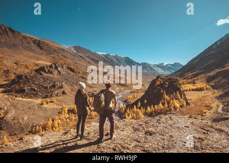 Two hikers stands on big rock and looks at mountains, river and valley - Stock Image