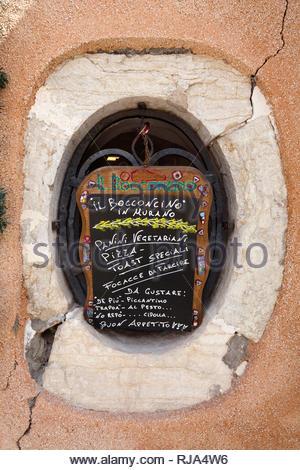 Holzbrett mit Speisenangebot im brüchigen Fensterrahmen in Murano - Stock Image