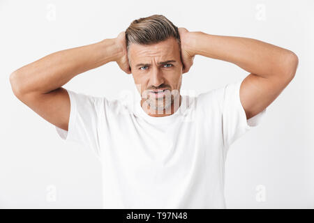 Image of unshaved man 30s with bristle wearing casual t-shirt posing on camera and covering ears due to noise isolated over white background - Stock Image