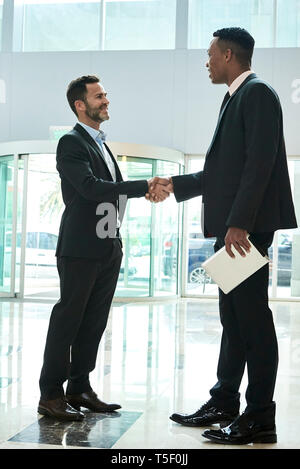 Businessmen shaking hands in hotel lobby - Stock Image