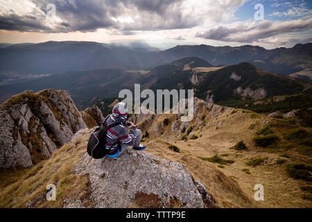 Rear view of male backpacker sitting on mountain against cloudy sky - Stock Image