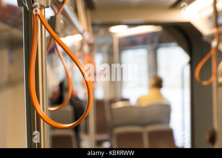 Orange hand holder in tram - Stock Image
