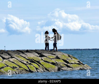 West Haven CT USA Armando Ortiz and Alisha Braacker enjoy the weather on the jetty near Savin Rock in West Haven. - Stock Image