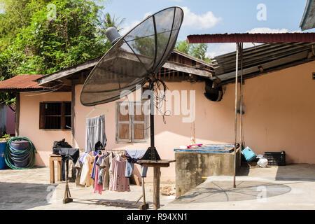 Large freestanding satellite dish outside a house at the Whisky village. Ban Xiang Hai, Luang Prabang, Louangphabang province, Laos, southeast Asia - Stock Image