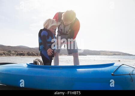 Father helping son adjust lifejacket in canoe, Loch Eishort, Isle of Skye, Hebrides, Scotland - Stock Image