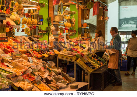 Woman buying fruit and vegetables from stall holder in Triana Market - Stock Image