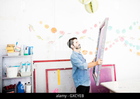 Young male printer holding up silkscreen in printing press studio - Stock Image