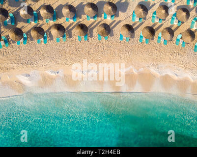 Sunbeds and umbrellas on a sandy beach with clear turquoise water in Greece - Stock Image