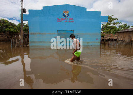 2015 flooding in Brazilian Amazon, young man passes in front of pentecostal church building Assembleia de Deus (Assembly of God) with the words 'Cristo é a Resposta' which means 'Christ is the answer', at Taquari district, Rio Branco city, Acre State. Floods have been affecting thousands of people in the state of Acre, northern Brazil, since 23 February 2015, when some of the state's rivers, in particular the Acre river, overflowed. Further heavy rainfall has forced river levels higher still, and on 03 March 2015 Brazil's federal government declared a state of emergency in Acre State, where cu - Stock Image