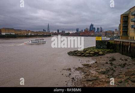River Thames at low tide, low water. Dec 2018 Looking towards the City of London from tow path at Canary Wharf - Stock Image