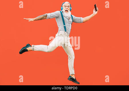 Senior crazy man jumping while listening music outdoor - Hipster male having fun dancing and celebrating life outside - Stock Image
