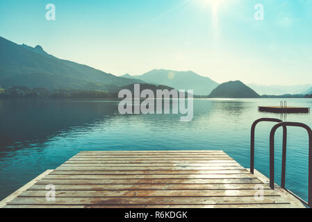 Wooden jetty for swimming in mountain lake in Austria. Swimming at early morning. European resort in mountains - Stock Image