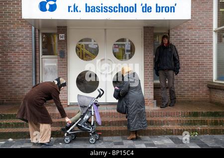 Amsterdam, oud west, moslima's wachten op hun kinderen bij de RK basisschool de bron - Stock Image