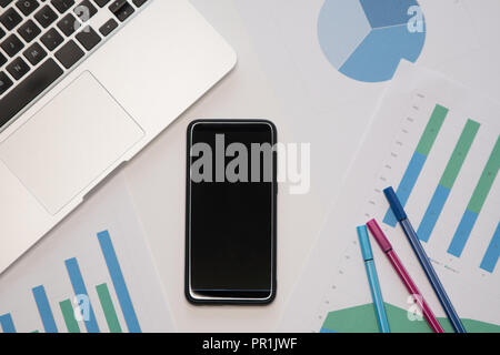 Modern workplace with smartphone, laptop. Business concept. Work papers with diagrams and graphs. - Stock Image