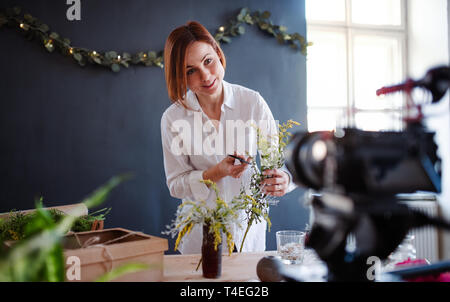 A young creative woman blogger or vlogger arranging flowers in a flower shop. A startup of florist business. - Stock Image