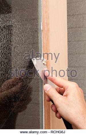 Glazing a Wooden Door - scraping excess putty from glass - Stock Image