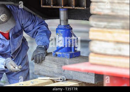 A man using a hydraulic jack and ratchet to lift up and secure a heavy load - Stock Image