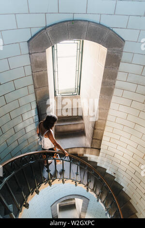 Penmarch, France - August 2, 2018: Woman going down the spiral staircase of Eckmuhl Lighthouse - Stock Image