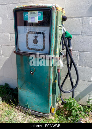 Disused green decaying petrol pump against a cinder block white painted wall - Stock Image