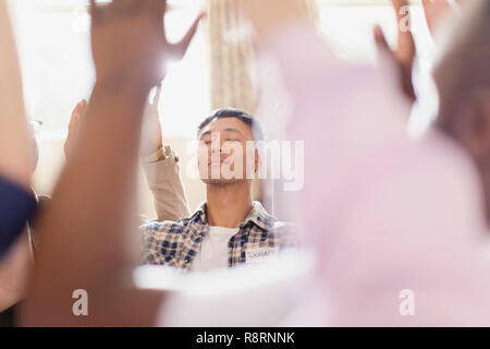 Serene man praying with arms raised in prayer group - Stock Image