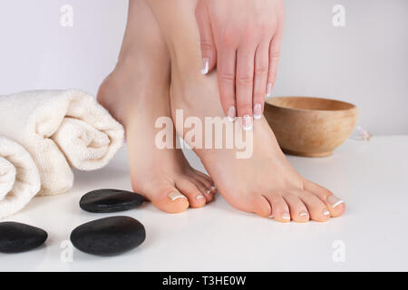 Woman bare feet and hands with french manicure and pedicure nails polish on towel in spa salon. Female beauty, femininity and spa concept. Close up - Stock Image