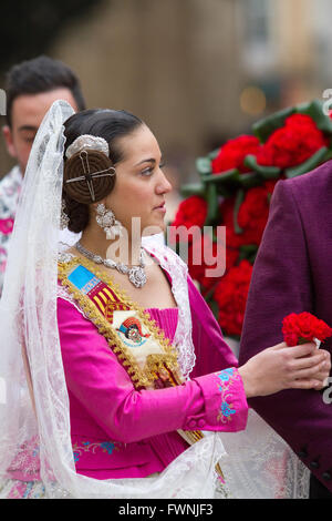 Woman in traditional costume handing flowers during the offering procession to the Lady of the Forsaken Valencia - Stock Image