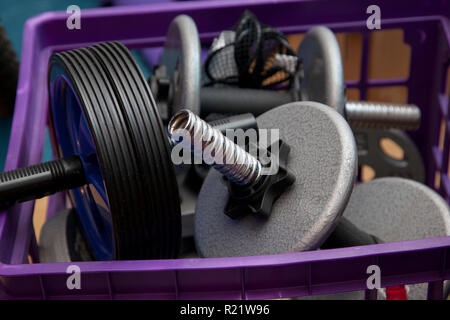 Metal workout weights in a milk crate box - Stock Image